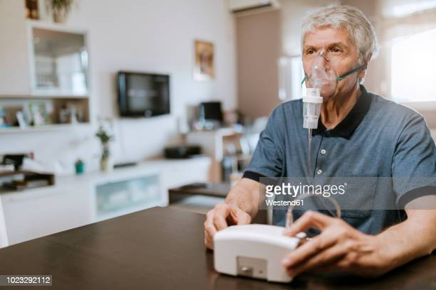 Senior man using inhaler at home