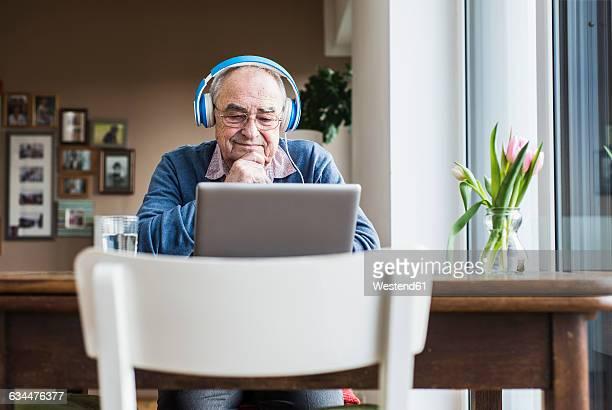 Senior man using laptop and headphones at home