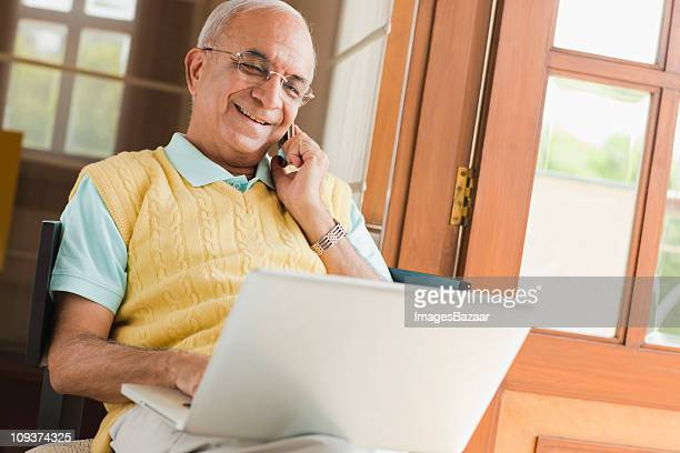 Senior man using laptop and mobile phone, smiling