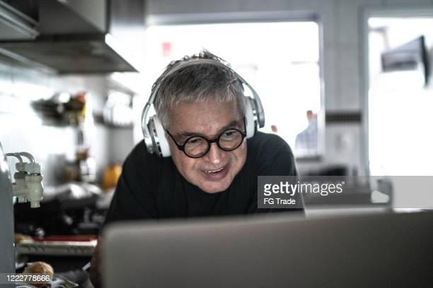 hogere mens die laptop thuis gebruikt - alleen seniore mannen stockfoto's en -beelden