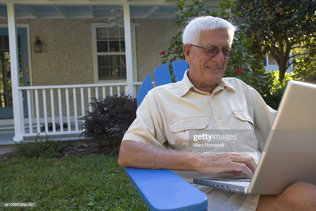 Senior man using laptop in front yard : Foto stock
