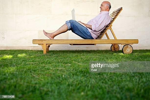 Senior Man Using Laptop in Garden