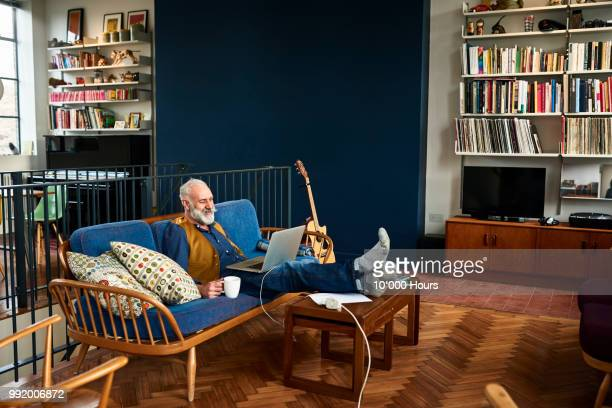 senior man using laptop in retro style living room - mood stream stock pictures, royalty-free photos & images