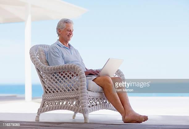 Senior man using laptop on beach patio