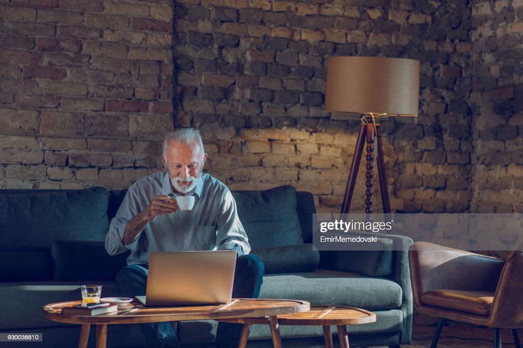 Senior man using laptop while relaxing at home : Stock Photo