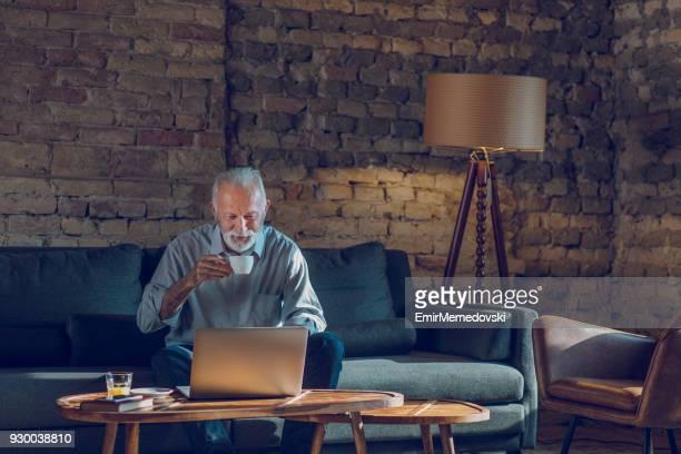 Ältere Mann mit Laptop beim Entspannen zu Hause