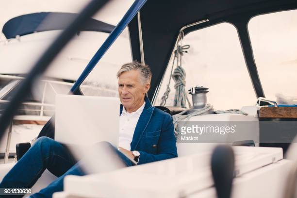 senior man using laptop while sitting in yacht during vacation - yacht foto e immagini stock