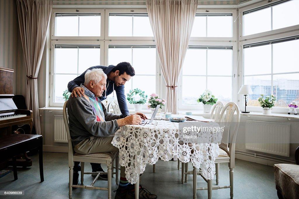 Senior man using laptop with caretaker at nursing home : Stock Photo