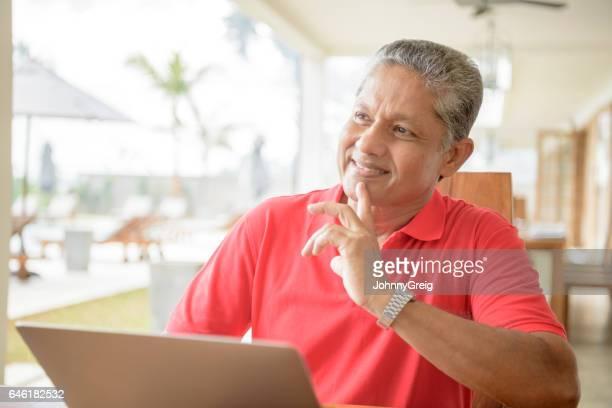 Senior man använder laptop med finger på hakan