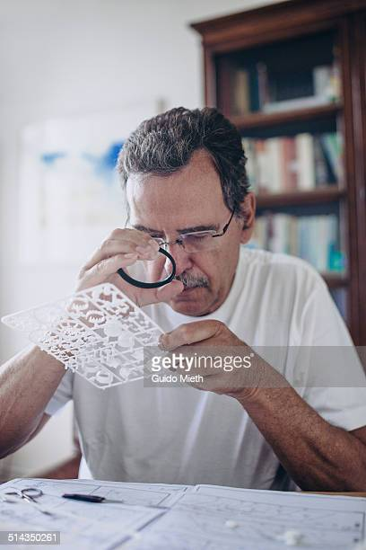 Senior Man using magnifying glass.