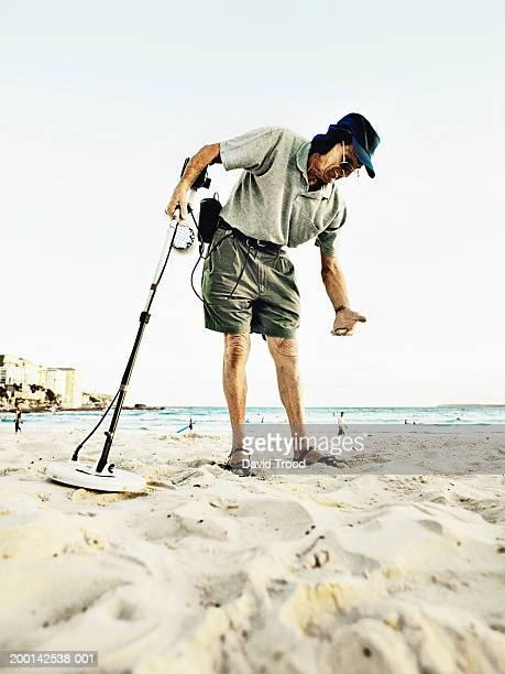 Senior man using metal detector on beach