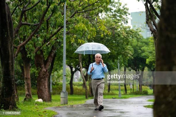 senior man using phone in park during rainy season - rainy season stock pictures, royalty-free photos & images