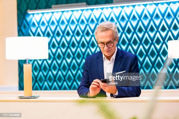 senior man using phone in the aiport vip lounge - izusek imagens e fotografias de stock