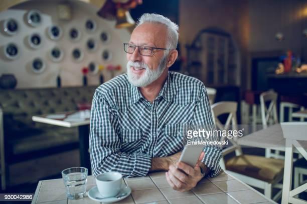 Senior man using smart phone in cafe