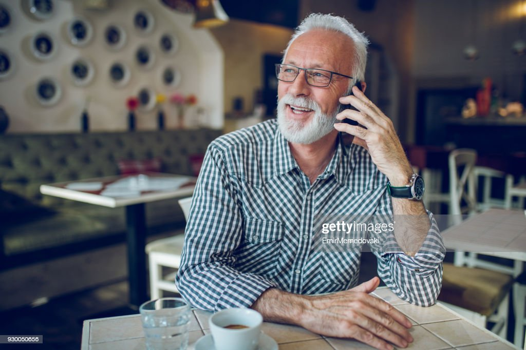 Senior man using smart phone in cafe : Stock Photo