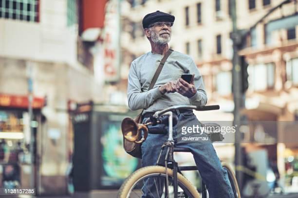 senior man met behulp van slimme telefoon tijdens het fietsen in de stad - nosotroscollection stockfoto's en -beelden