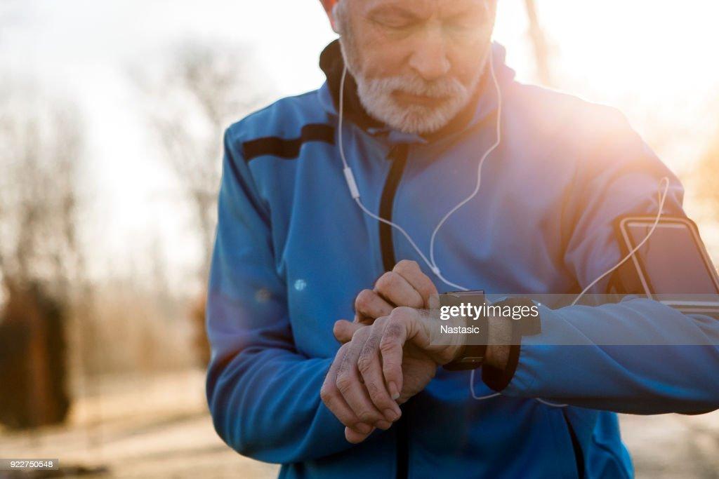 Senior Man met behulp van Smart Watch meten van de hartslag : Stockfoto