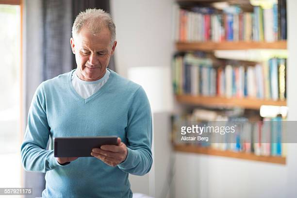 senior man using tablet computer at home - regarder vers le bas photos et images de collection