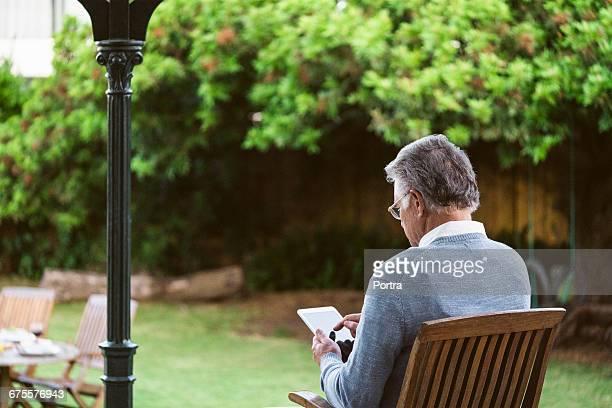 Senior man using tablet while sitting at park
