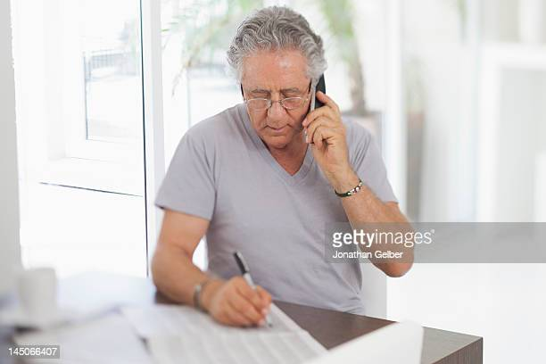 A senior man using the phone and writing on a document