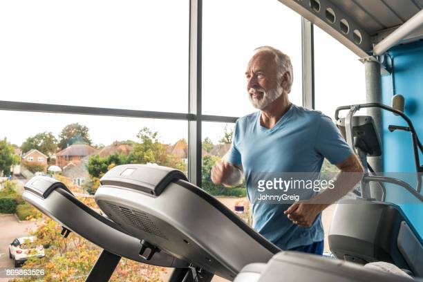 Senior man using treadmill in gym wearing blue t shirt