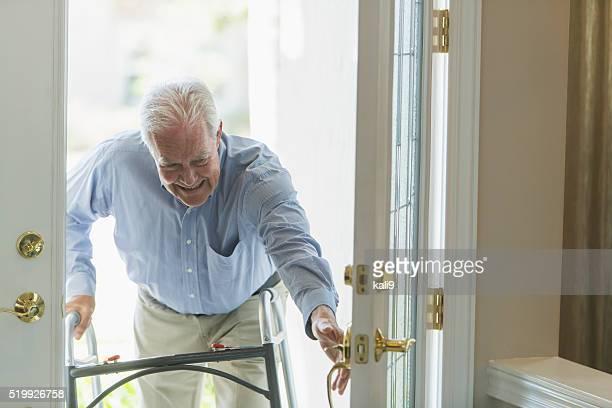 Alter Mann mit Walker, Sie kommen nach Hause an Tür
