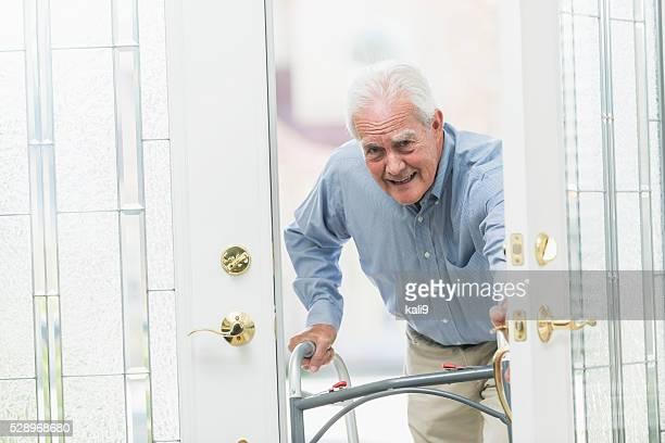 Senior man using walker, coming home through front door