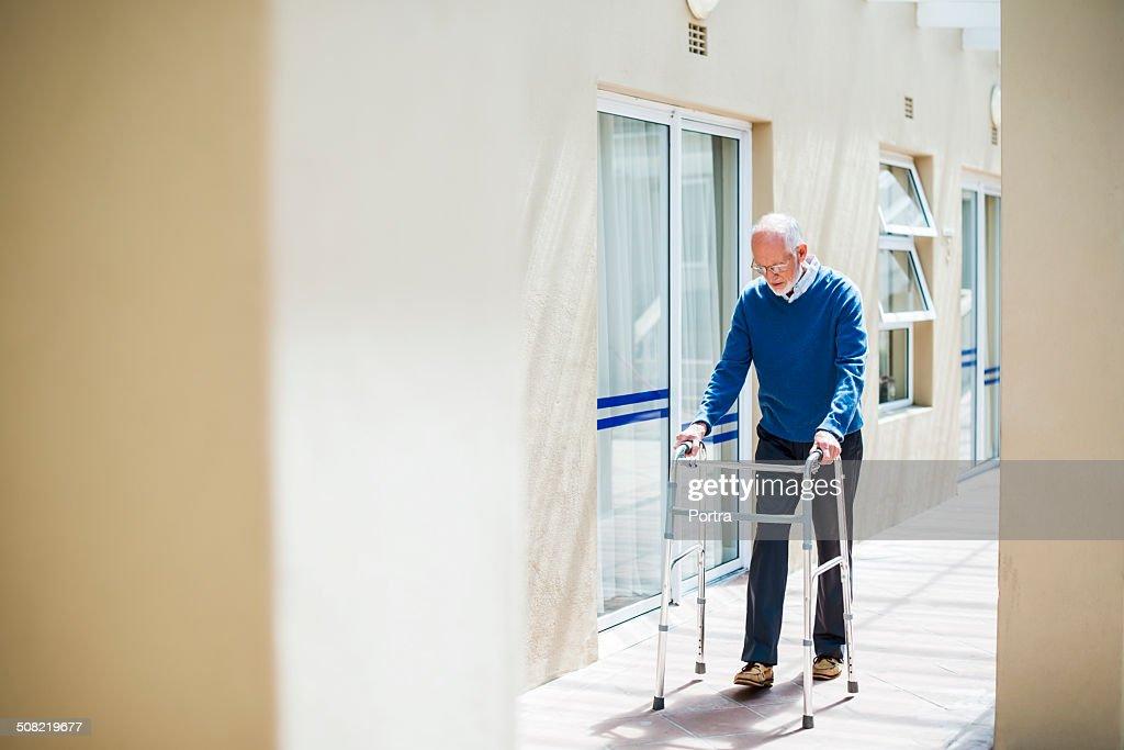 Senior man using walker on sidewalk : Stock Photo