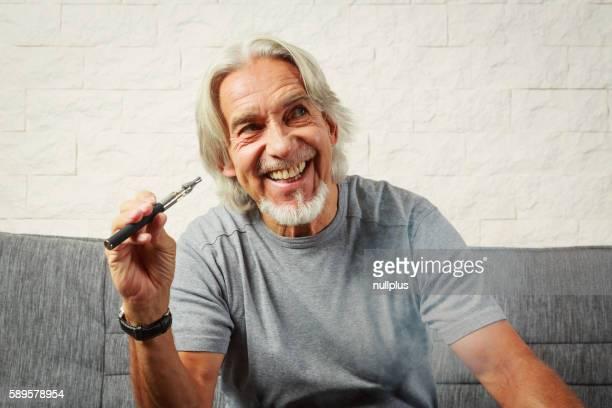 Senior man vaping, enjoying an electronic cigarette