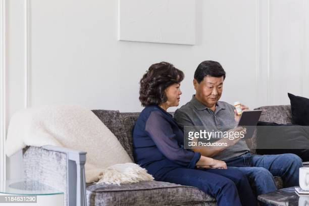 senior man video chats with healthcare professional - telemedicine stock photos and pictures