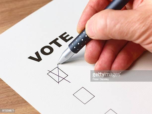 Senior man voting with cross