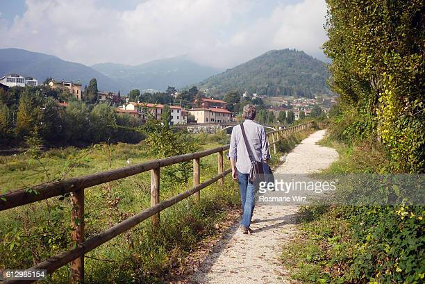 Senior man walking along footpath in Seriana Valley, Italy.