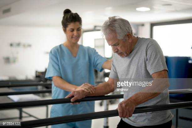 senior man walking between parallel bars in physiotherapy and therapist next to him helping - parallel bars gymnastics equipment stock photos and pictures