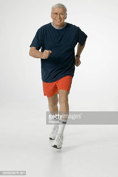 Senior man walking in studio, portrait