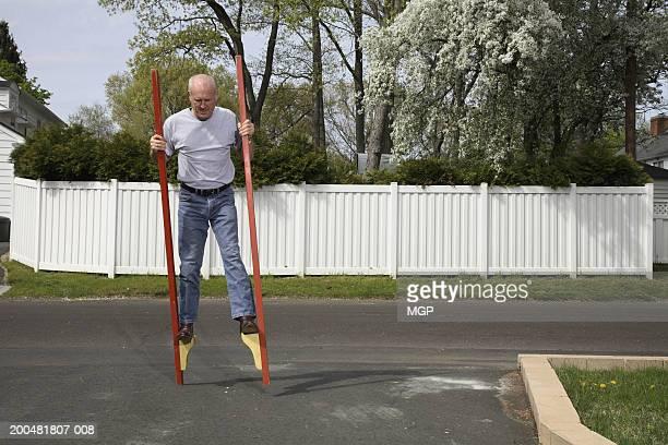 Senior man walking on stilts