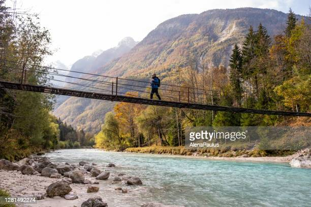 senior man walking on the suspension bridge over the soča river - slovenia stock pictures, royalty-free photos & images