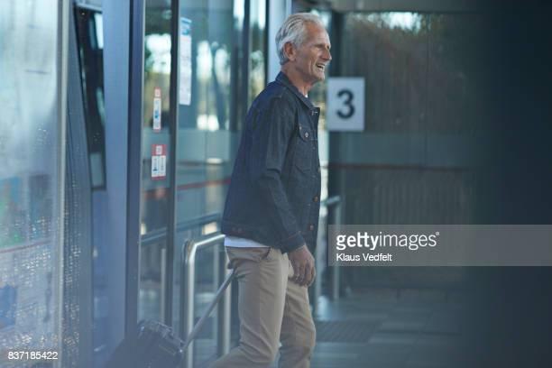 Senior man walking out of bus, on to public transport platform