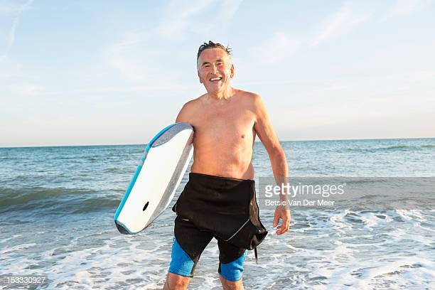 Senior man walking out of sea with body board.