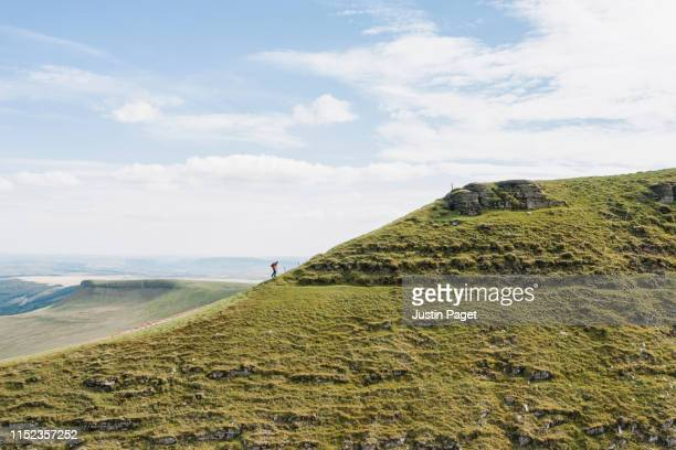 senior man walking to summit of pen y fan - moving up stock pictures, royalty-free photos & images