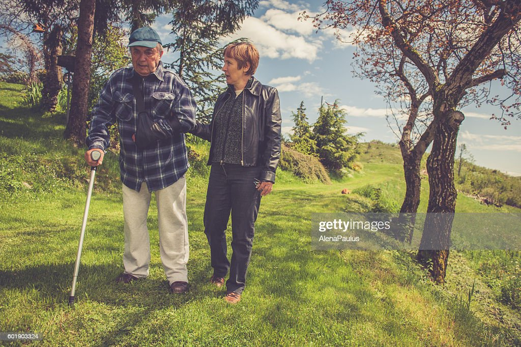 Senior Man walking with Crutch and Helped by his Daughter : Stock Photo