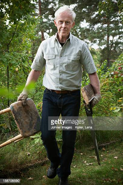 Senior man walking with holding saw and stool