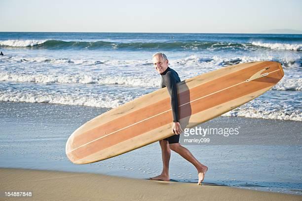 senior man walking with surfboard by ocean