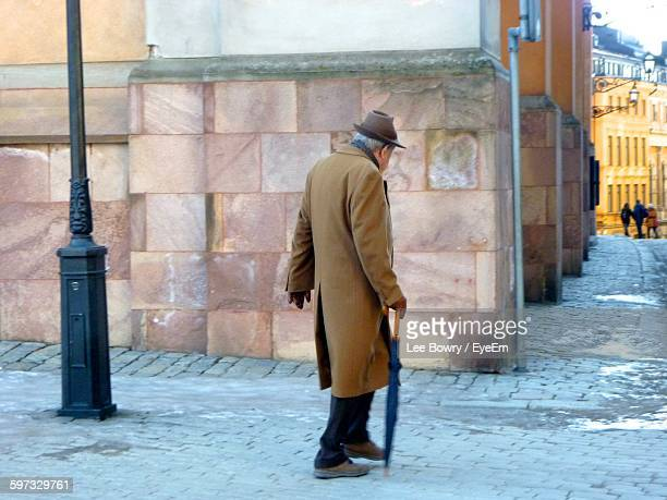 Senior Man Walking With Umbrella On Footpath In City