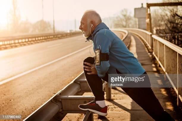 uomo anziano che si scalda per fare jogging su un ponte della città - 60 69 anni foto e immagini stock