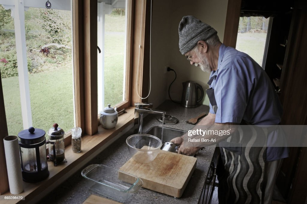 Senior man washing up dishes : Stock Photo