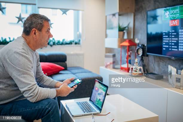 senior man watches soccer game and bets in his living room - gambling addiction stock pictures, royalty-free photos & images