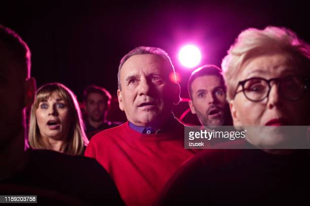 senior man kijken naar een interessante film in de bioscoop - izusek stockfoto's en -beelden