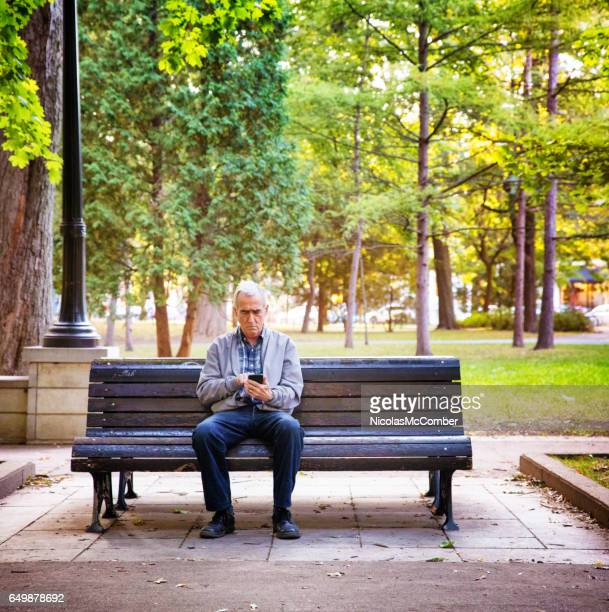 Senior man watching media on mobile phone alone in a public park