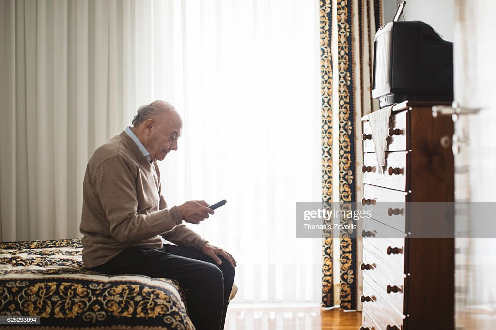Senior man watching television : Stock Photo