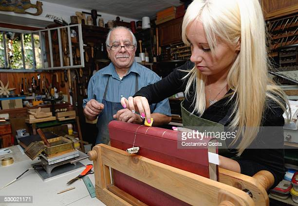 Senior man watching trainee applying gold leaf to book spine in traditional bookbinding workshop